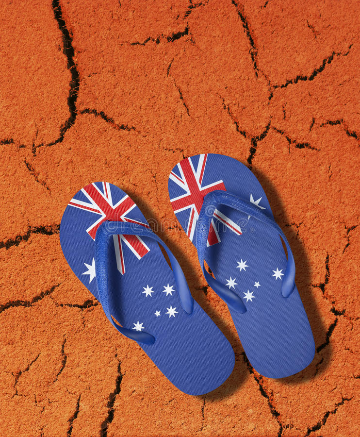 Australian Flag Thongs Icon. Thongs with an Australian flag pattern resting on a rich red outback soil background stock photography