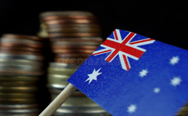 Australian flag waving with stack of money coins. Macro stock photo