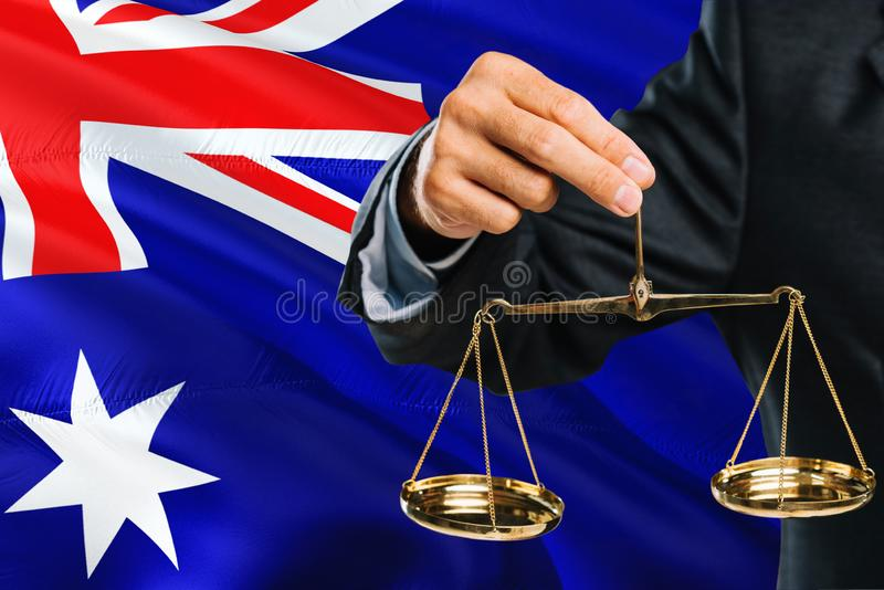 Australian Judge is holding golden scales of justice with Australia waving flag background. Equality theme and legal concept royalty free stock photography