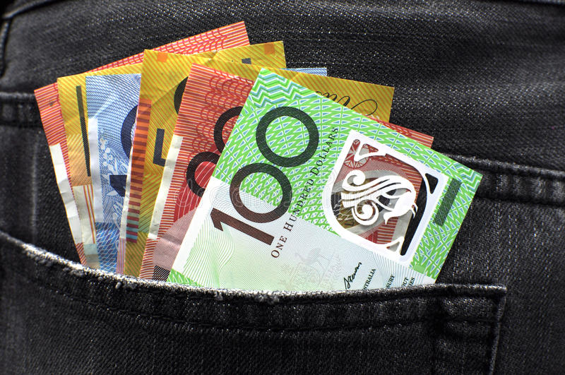 Australian money in jeans back pocket. Australian money including 100, 50, 5, 10 and 20 dollar notes, in back pocket of a man's black charcoal jeans pocket stock images