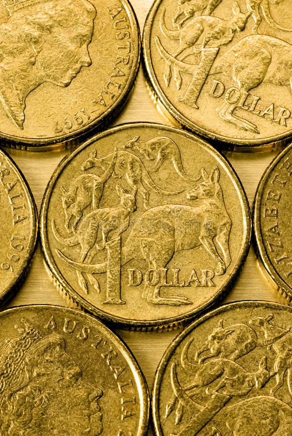Australian One Dollar Coins. On a gold background stock photo