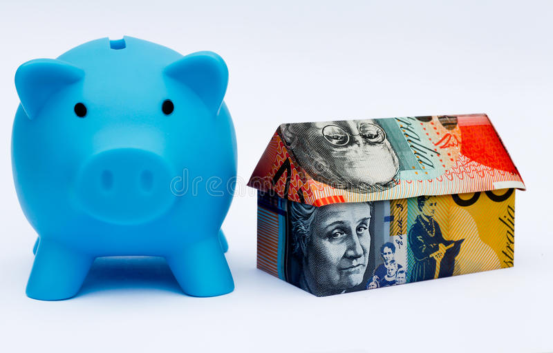 Australian Origami Money House with Piggy bank. Origami money house next to a blue piggy bank royalty free stock image