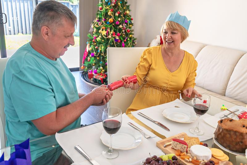 Australian senior couple pulling Christmas cracker. While sitting behind dressed table before dinner stock photo