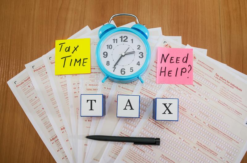 Australian tax forms with pen and blue alarm clock on the table. View from above. Tax concept. The word tax on cubes. Australian tax forms with pen and blue royalty free stock photos