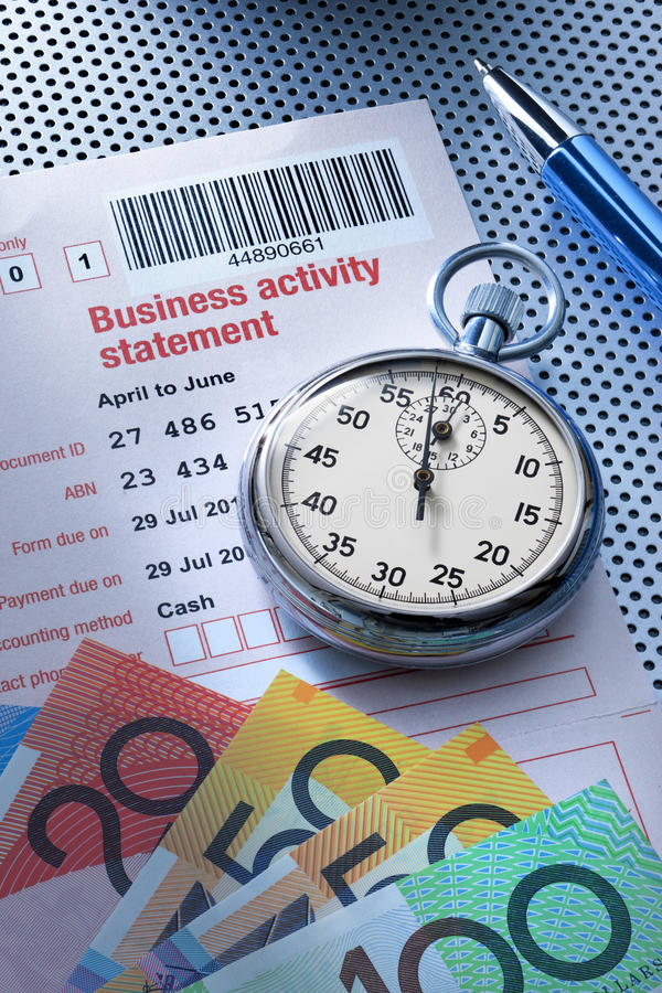 Australian Tax Taxes Time Money. An Australian business activity tax statement form with a stopwatch and money royalty free stock photo