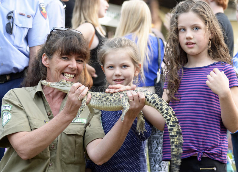 Australian wildlife woman park ranger teaching children about native crocodiles at local fair. An Australian wildlife woman park ranger enjoying herself royalty free stock photos