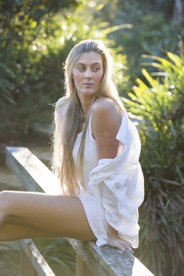 Australiano con capelli biondi lunghi che si siedono sul distogliere lo sguardo del ponte fotografie stock