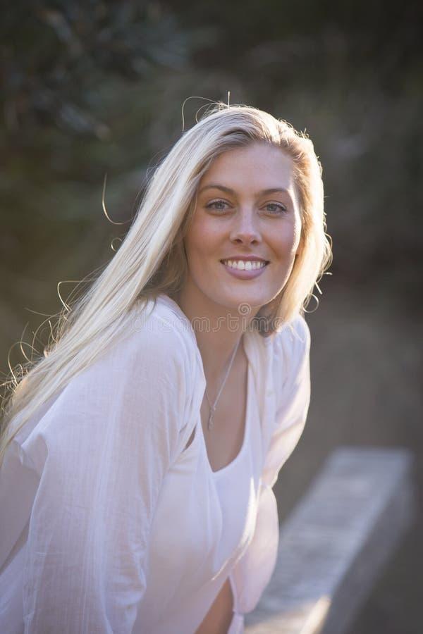 Australiano con capelli biondi lunghi che si siedono sullo sguardo del ponte alla macchina fotografica fotografia stock