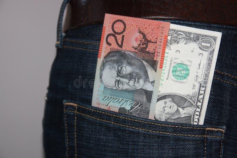 Australiano e dólares americanos no bolso das calças de brim fotografia de stock royalty free