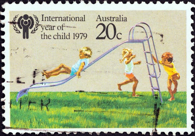AUSTRALIEN - CIRCA 1979: Ein Stempel, der in Australien gedruckt wird, zeigt die Kinder, die auf Dia, circa 1979 spielen lizenzfreies stockbild
