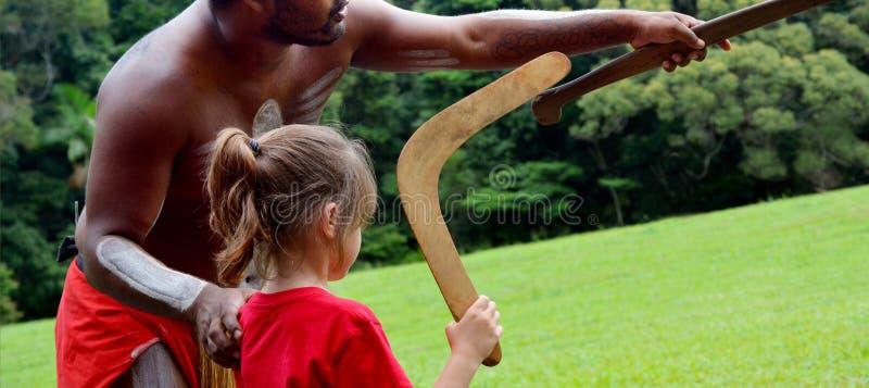 Australieraboriginermannen undervisar en ung flicka hur man kastar a royaltyfria bilder