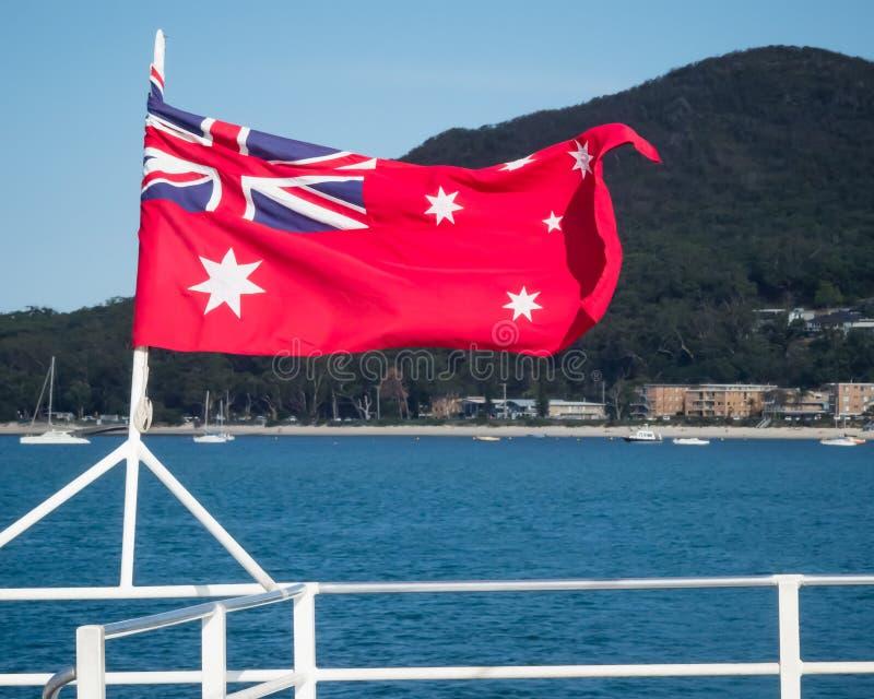 Australijski czerwony chorąży flagi latanie od srogo łódź z naturalną sceną w tle zdjęcia stock