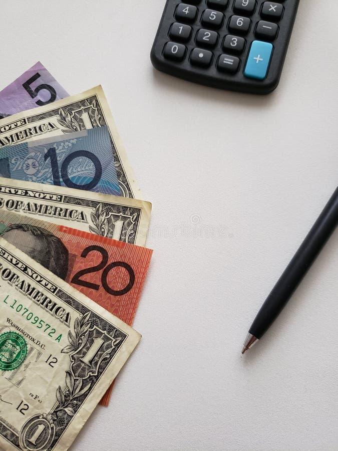 Australische bankbiljetten, Amerikaanse dollarrekeningen, calculator en zwarte pen op witte achtergrond stock fotografie