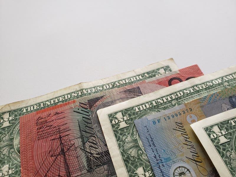 Australische bankbiljetten en Amerikaanse dollarrekeningen op witte achtergrond stock foto