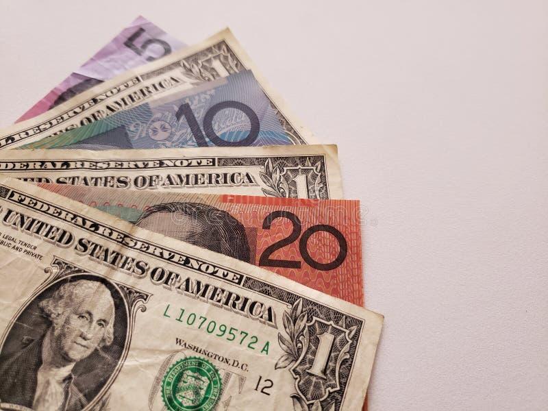 Australische bankbiljetten en Amerikaanse dollarrekeningen op witte achtergrond stock afbeeldingen