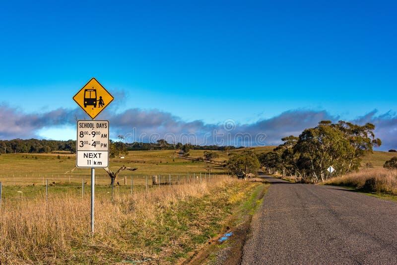 Australische binnenlandweg met het teken van de schoolbushalte stock fotografie