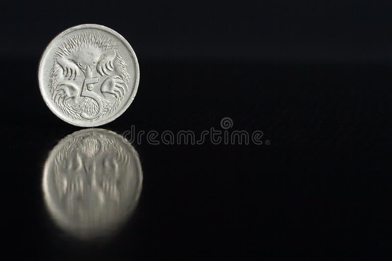 Australische Cents 1987 der Münze fünf auf dem Rand auf schwarzem Hintergrund mit Reflexion lizenzfreies stockbild