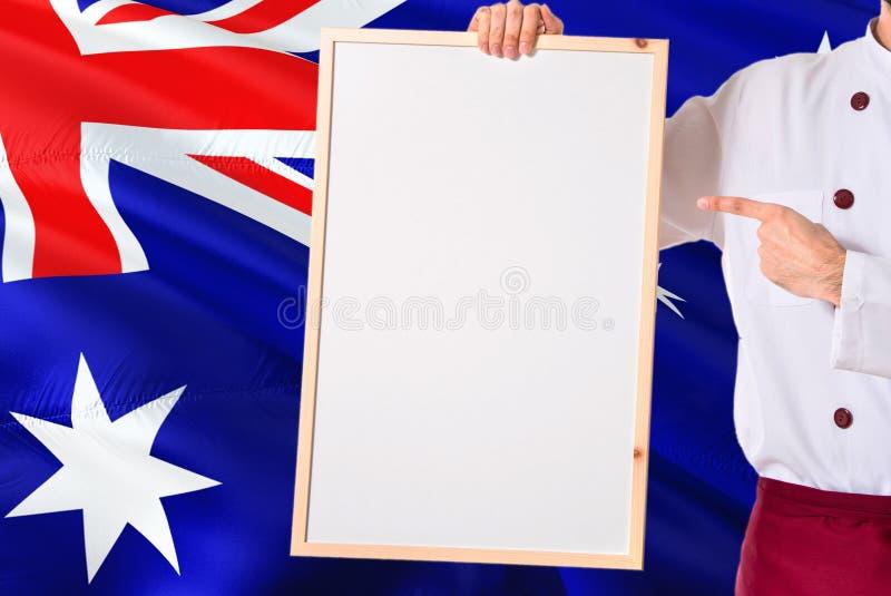 Australische Chef-kok die leeg whiteboardmenu op de vlagachtergrond van Australië houden Kok die eenvormige richtende ruimte voor stock foto