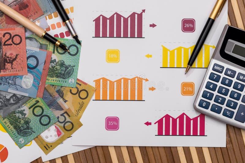 Australische dollarbankbiljetten op bedrijfsgrafieken met calculator en pen stock afbeeldingen