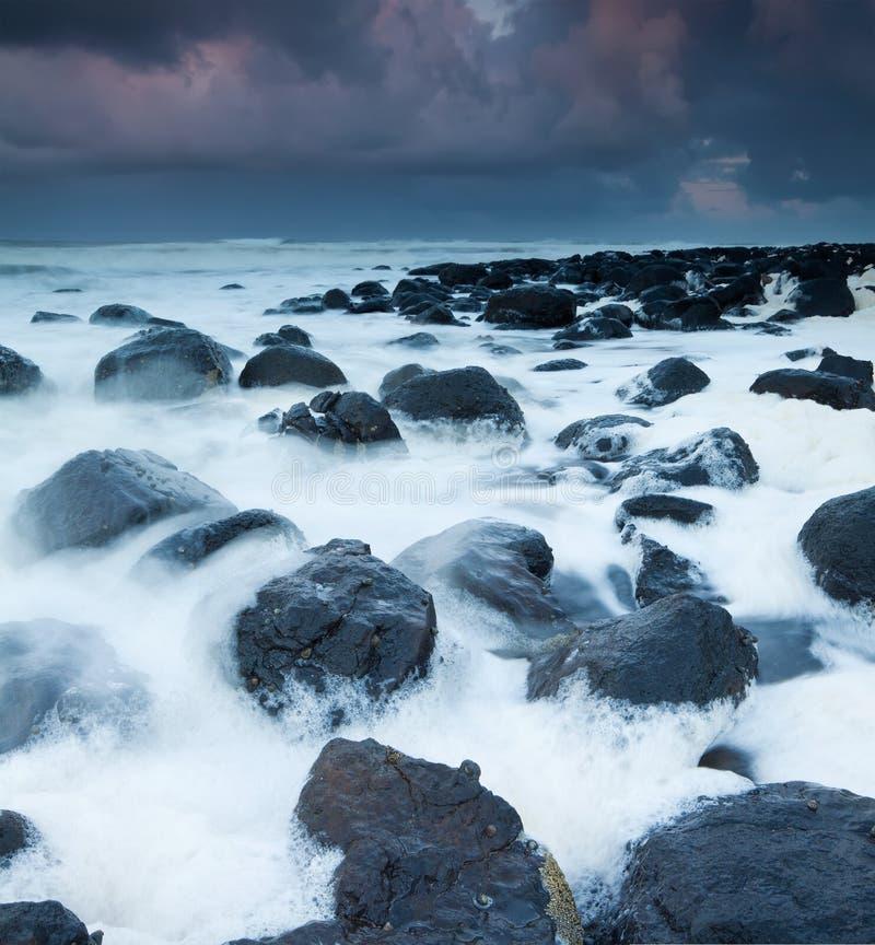 Australische Küste voll des Schaumgummis an der Dämmerung stockfoto