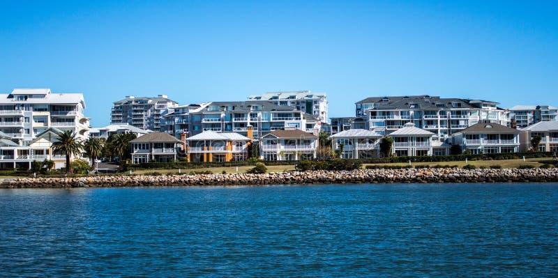Australische Uferhäuser und -kondominien mit Felsendamm gegen blauen Himmel lizenzfreies stockbild