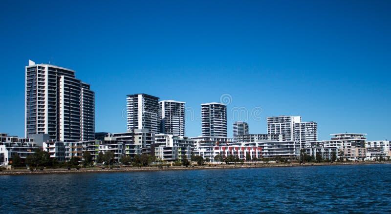 Australische Uferhäuser und -kondominien mit Felsendamm gegen blauen Himmel lizenzfreie stockfotografie
