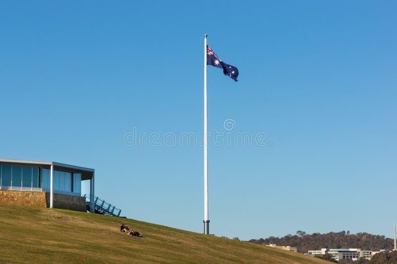 Australisches Flaggen-Fliegen auf grasartigem Hügel lizenzfreies stockbild