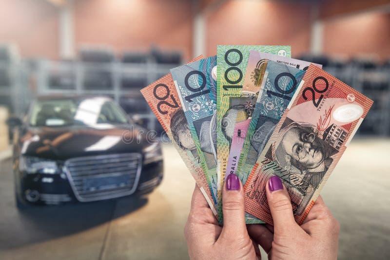 Australisk dollar i händer på bakgrund av nya bilar royaltyfri bild