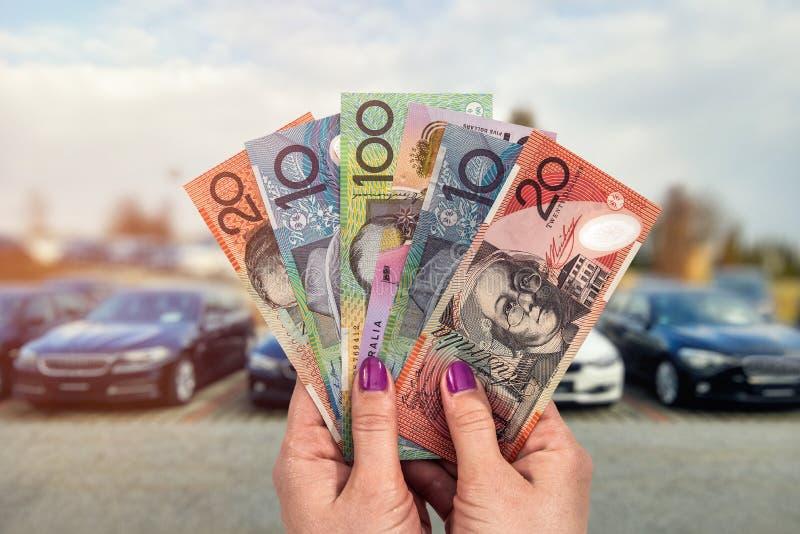Australisk dollar i handbakgrund av nya bilar arkivbilder