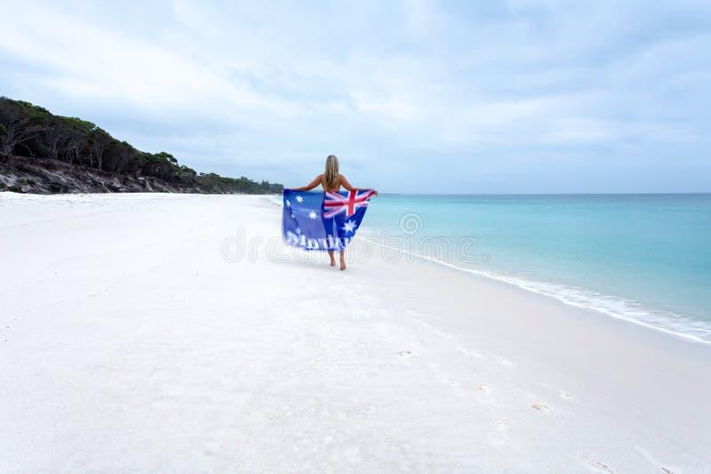 Australisk flicka som promenerar den ursprungliga stranden med den australiska flaggan royaltyfria bilder
