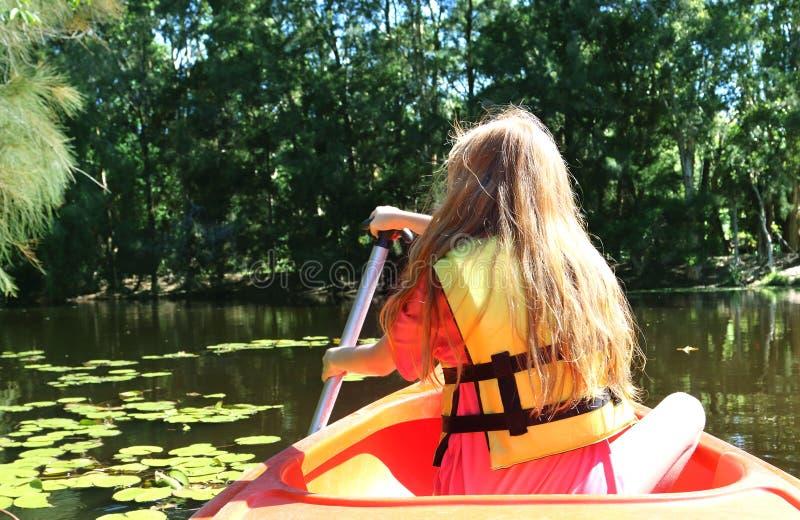 Australisk flicka som tycker om kajakritt på det härliga dammet arkivbild