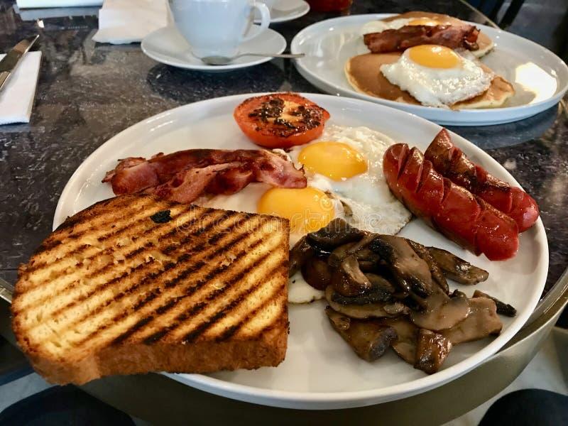 Australisk/australisk frukost med rostat bröd, Fried Eggs, den frasiga baconkorven, champinjoner och salta pannkakor royaltyfri fotografi