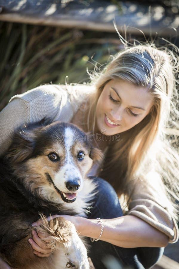 Australisk skönhet med långt blont hår sitter med hennes colliehund arkivfoton