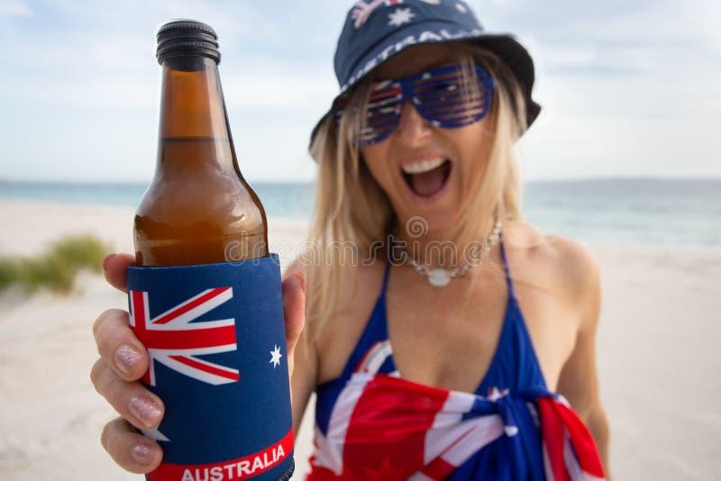 Australiskt kvinnainnehav som erbjuder en flaska av öl royaltyfri bild