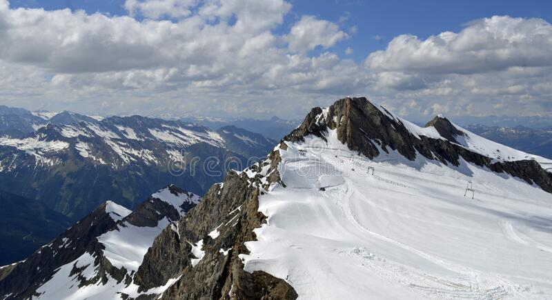 Austria europe mountain tops with snow on it and clouds and blue sky. Austria europe mountain tops with snow on it and clouds stock image