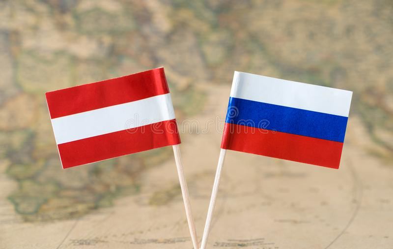 Austria and Russia flag pins on a world map, political or diplomatic relations concept. Paper flag pins of Austria and Russia on a world map background. Concept stock image