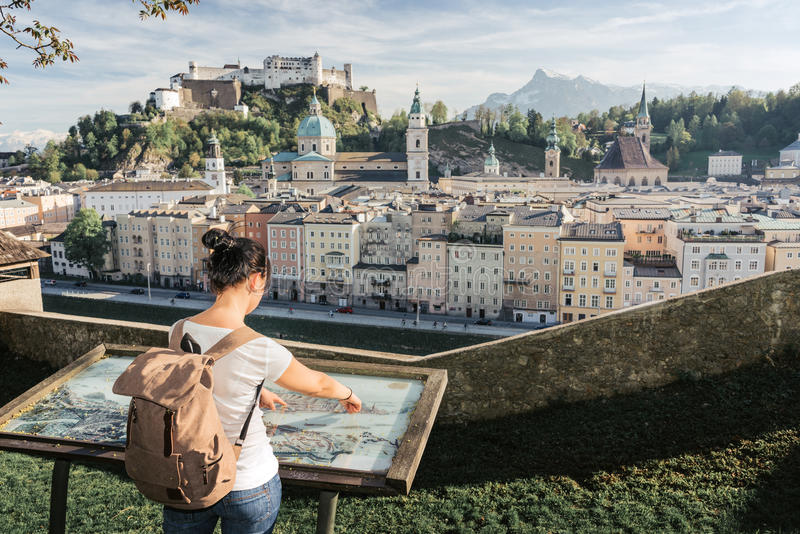Austria. Salzburg. The girl tourist on the observation deck. At the old maps of the city with views of the Hohensalzburg fortress royalty free stock image
