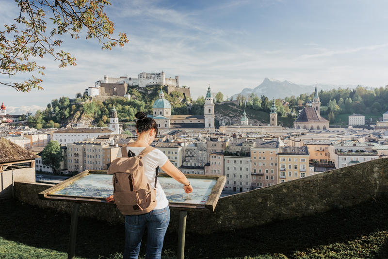 Austria. Salzburg. The girl tourist on the observation deck. At the old maps of the city with views of the Hohensalzburg fortress.tif stock photography