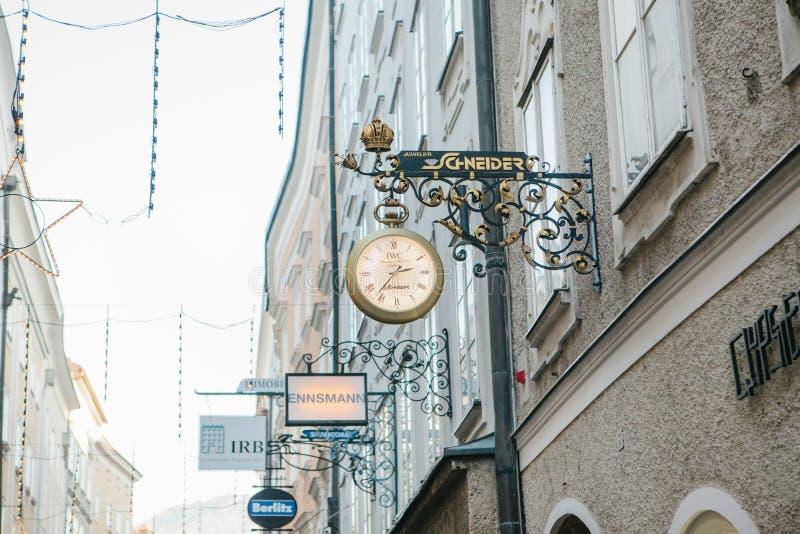 Austria, Salzburg, Styczeń 1, 2017: Reklamowi znaki sklepy na Getreidegasse ulicie Malownicza ulica w starym zdjęcie stock