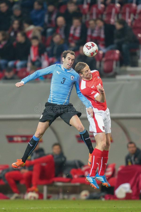 Austria vs. Uruguay. KLAGENFURT, AUSTRIA - MARCH 05, 2014: Diego Godin (#3 Uruguay) and Marc Janko (#21 Austria) fight for the ball in a friendly soccer game royalty free stock images