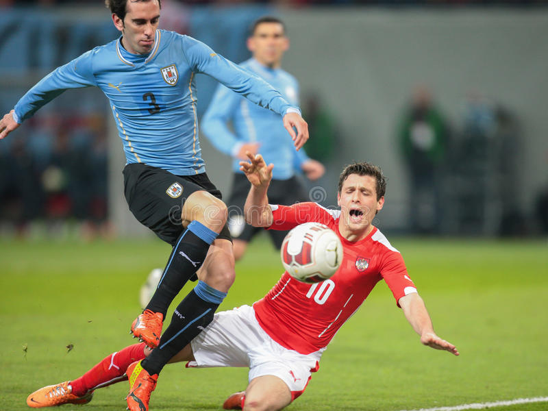 Austria vs. Uruguay. KLAGENFURT, AUSTRIA - MARCH 05, 2014: Diego Godin (#3 Uruguay) and Zlatko Junuzovic (#10 Austria) fight for the ball in a friendly soccer stock photos