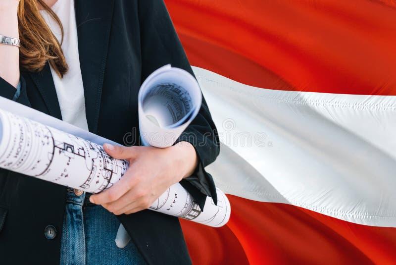 Austriacki architekt kobiety mienia projekt przeciw Austria falowania flagi tłu Budowy i architektury poj?cie zdjęcie stock
