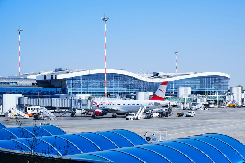 Austrian Airlines airplane docked to a passengers boarding bridge at Henri Coanda International Airport Bucharest on a clear day. Otopeni, Romania - September stock photos