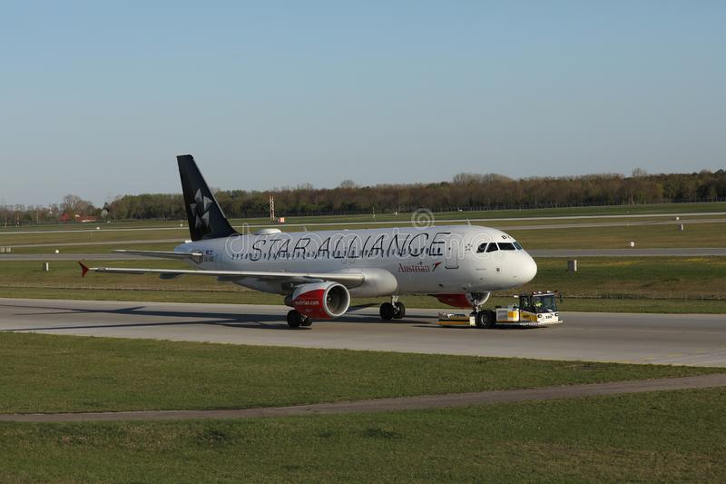 Austrian Airlines Star Alliance plane being towed. Austrian Airlines plane taxiing on taxiway. Star Alliance livery stock images