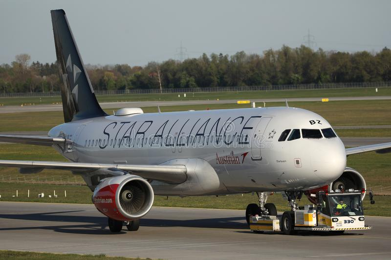 Austrian Airlines Star Alliance plane being towed. Austrian Airlines plane taxiing on taxiway. Star Alliance livery royalty free stock images