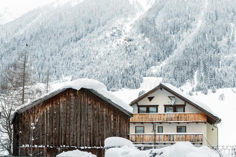 Austrian alpine village scenic landscape with small chalet and wooden barn ,pine forest trees and snow covered mountains on. Background. Cold frosty weather royalty free stock image