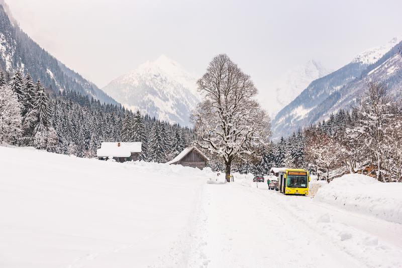 Austrian bus and wooden house. Mountains at the background. Ski region Schladming-Dachstein, Liezen District, Styria, Austria royalty free stock photo