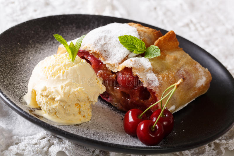 Austrian cuisine: cherry strudel with vanilla ice cream close-up on a plate. Horizontal royalty free stock photos