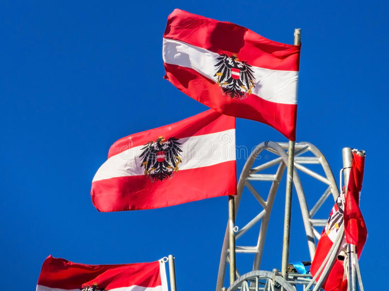 Austrian flag. Several flags of austria with the national coat of arms flap in the wind. above blue sky stock photography