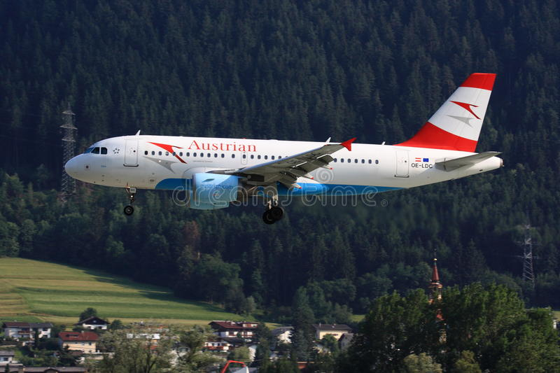 Austrian A319 landing. An Austrian Airlines Airbus A319 is landing at Innsbruck airport, hillside in the background stock photo